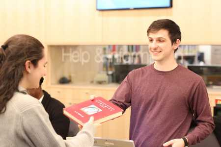 Student worker helping library user