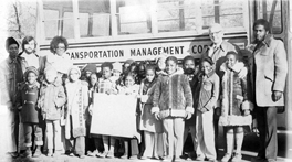Students and Metropolitan Council for Educational Opportunity staff pose in front of a bus, 1976
