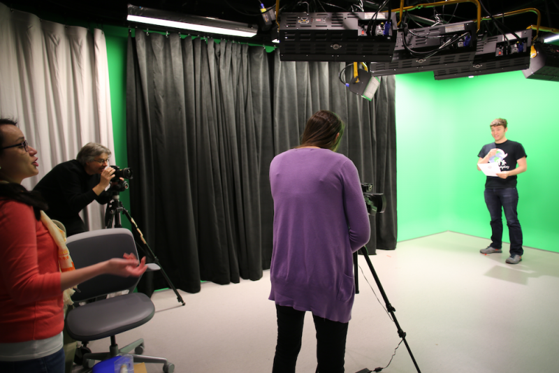 People film a scene with a green screen in the Video Recording Studio