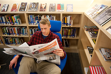 Student reading a newspaper in the Hub